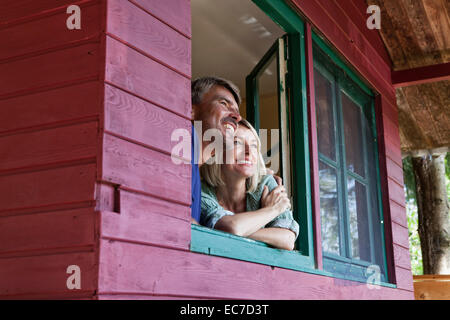 Happy mature couple looking out of window of summer house - Stock Photo