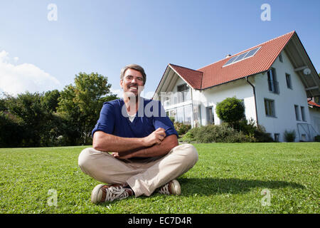Smiling man sitting on lawn in garden - Stock Photo