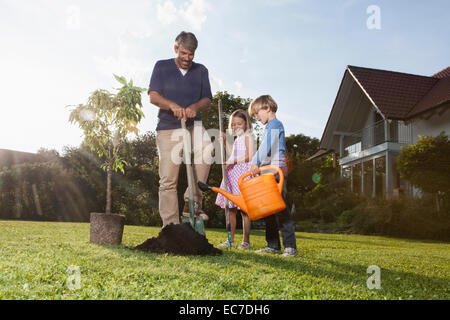 Father and children planting tree in garden - Stock Photo