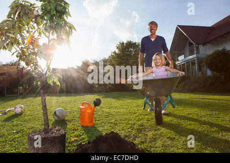 Father with daughter in wheelbarrow planting tree in garden - Stock Photo