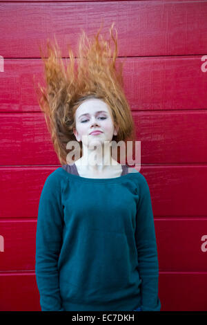 Portrait of teenage girl tossing her hair in front of red wooden wall - Stock Photo