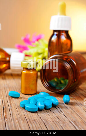 some bottles with different alternative remedies on a rustic wooden table - Stock Photo