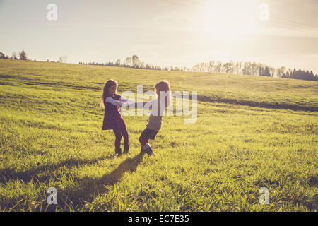 Two little girls turning around together on a meadow in backlight - Stock Photo
