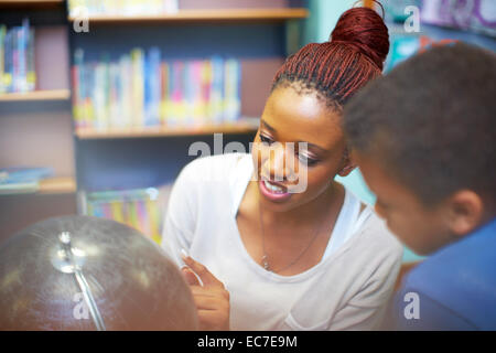 Young woman and boy looking at globe in library - Stock Photo