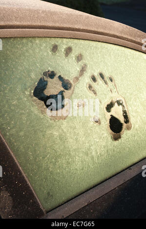 hand print like foot prints melted frost on window to car idea of trapped inside surviving cold spell call for help - Stock Photo