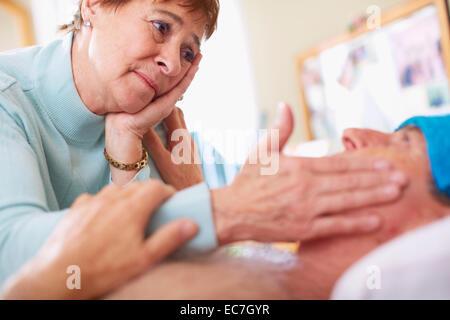 Senior woman caring for sick husband at home - Stock Photo