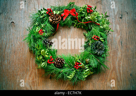 a natural christmas wreath with pine cones, berries and a red ribbon bow hanging on a rustic door - Stock Photo
