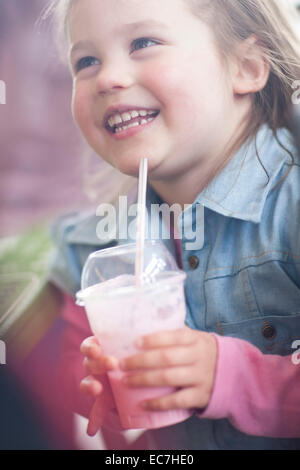 Portrait of smiling little girl with milkshake cup in coffee shop - Stock Photo