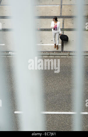 Young businesswoman with smartphone and wheeled luggage, elevated view - Stock Photo