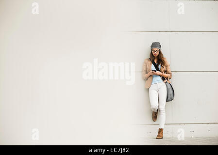 Young woman leaning against a wall waiting - Stock Photo
