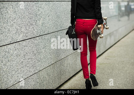 Young woman with bag and skateboard wearing red trousers, partial view - Stock Photo