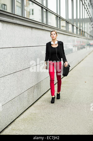 Young businesswoman with skateboard and headphones wearing red trousers - Stock Photo