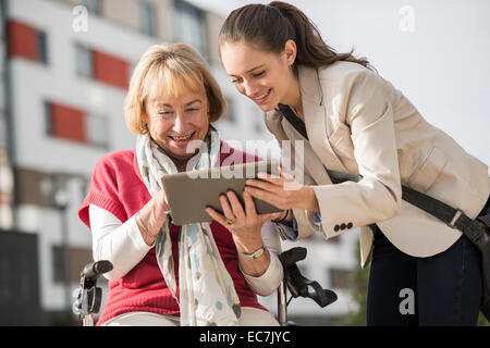 Granddaughter and her grandmother looking at digital tablet - Stock Photo