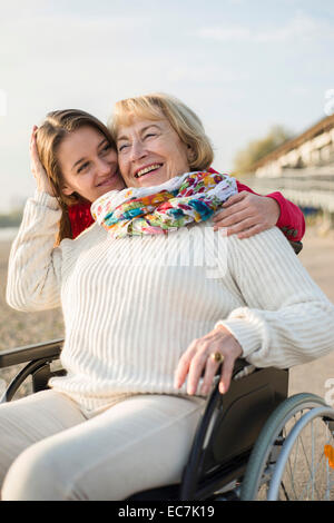 Young woman head to head with her laughing grandmother sitting in wheelchair - Stock Photo