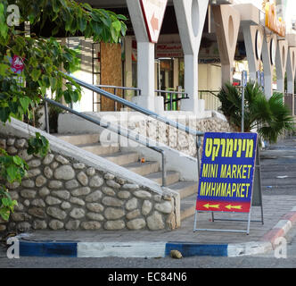 Hebrew; English and Russian sign at a parade of shops in the Ein Bokek hotel and resort village on the Israeli shore - Stock Photo