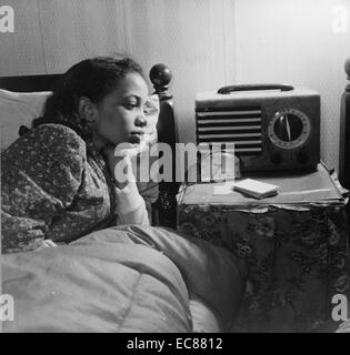 Photograph of an African-American woman listening to the radio during World War Two. Dated 1943 - Stock Photo