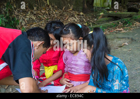 Three Balinese girls attending an outdoor school class, Bali, Indonesia - Stock Photo
