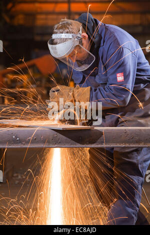 A craftsman wearing personal safety equipment while working with steel and hand tools in an industrial workshop - Stock Photo