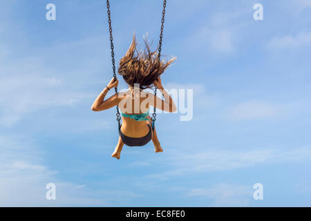 LOS ANGELES, CA – JULY 11 : Young girl on a swing looking out over the ocean in Los Angeles, California on July, - Stock Photo