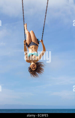LOS ANGELES, CA – JULY 11 : Young girls on a swing looking out over the ocean in Los Angeles, California on July, - Stock Photo