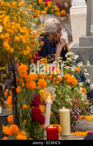 An elderly woman reflects at the gravesite of her deceased husband decorated at Xoxocatian cemetery decorated with - Stock Photo