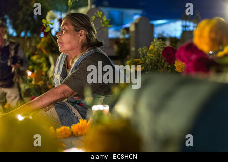 An elderly woman reflects at the gravesite of a relative at Xoxocatian cemetery decorated with flowers and candles - Stock Photo