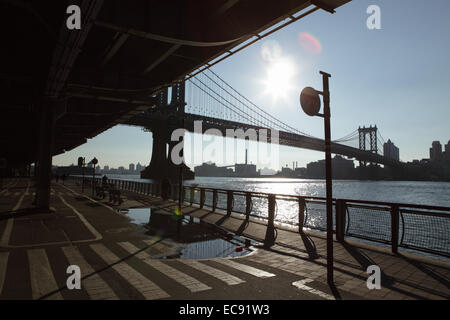 East River Esplanade as the sun rises over the Manhattan Bridge and Brooklyn - Stock Photo