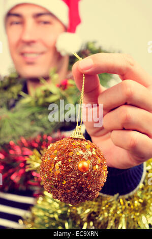 a young man wearing a santa hat covered with christmas ornaments and holding a bauble in his hand - Stock Photo