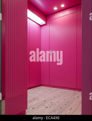 Corrugated, pink wood panelling in hallway with pine flooring - Stock Photo