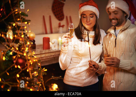 Santa man and woman with champagne looking at Bengal light on xmas night - Stock Photo