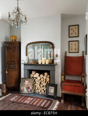 Vintage rug on wooden floor in front of fireplace with logs and ...