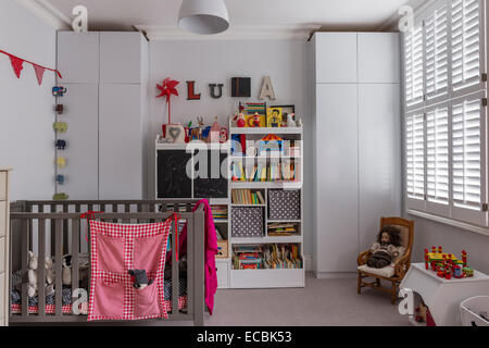 Childs bedroom with cot and inbuilt storage - Stock Photo