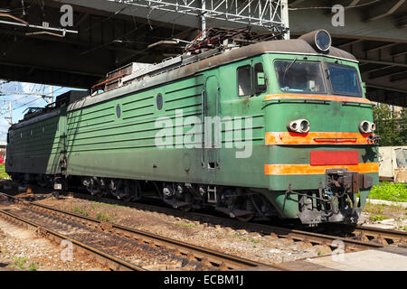 Green modern Russian locomotive with red stripes on the cabin stands on the railway station - Stock Photo