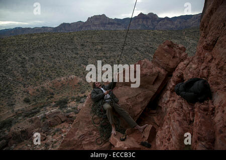 Young man belays a climber at Red Rocks in Las Vegas, NV. - Stock Photo