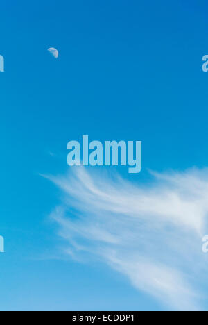 Half Moon and Wispy Clouds in Blue Sky - Stock Photo