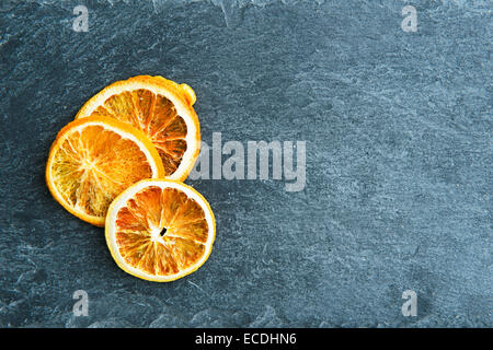 Closeup on dried orange slices on stone substrate - Stock Photo