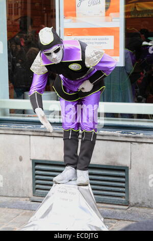 Street mime performer man in violet dress and white painted face. Brussels, Belgium - Stock Photo