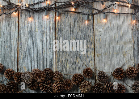 Copy Space Christmas Lights And Pinecones On Rustic Wood Background