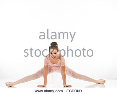 10 year old girl doing the splits pose in a tutu on a white background. - Stock Photo