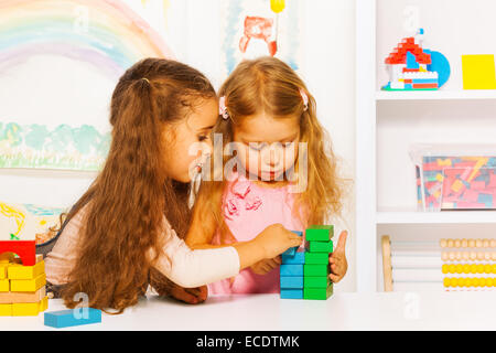 Couple little girls playing stacking wooden blocks - Stock Photo