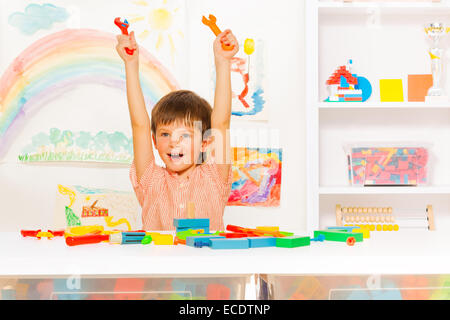 Cute happy boy with wrenches in the kindergaten - Stock Photo