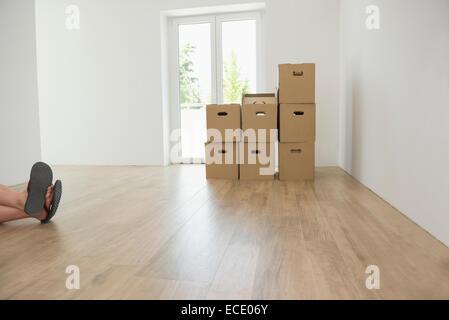 Empty room cardboard boxes wooden floor feet - Stock Photo