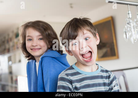 Boy making funny faces while girl in background - Stock Photo