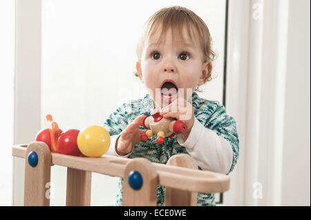Portrait 1 year old baby girl playing toy
