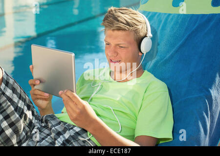 Young male swimming pool tablet computer portrait - Stock Photo