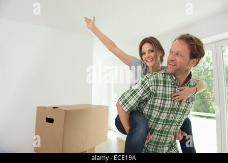 Woman piggyback man new house happy - Stock Photo