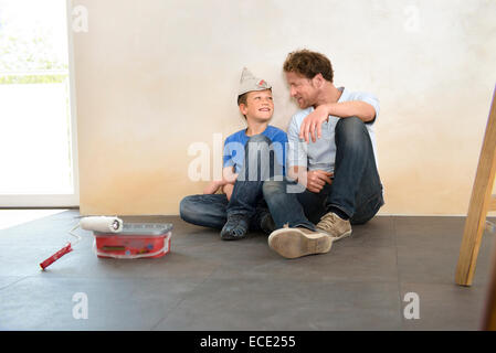 Father son working taking a break decorating - Stock Photo