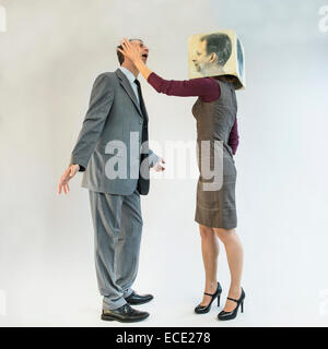 Businessman getting slapped by businesswoman wearing mask - Stock Photo