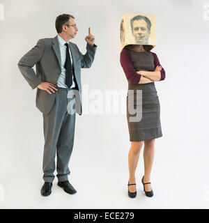 Businessman scolding businesswoman wearing mask - Stock Photo