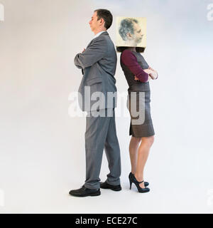 Businessman standing back to back of businesswoman wearing mask - Stock Photo